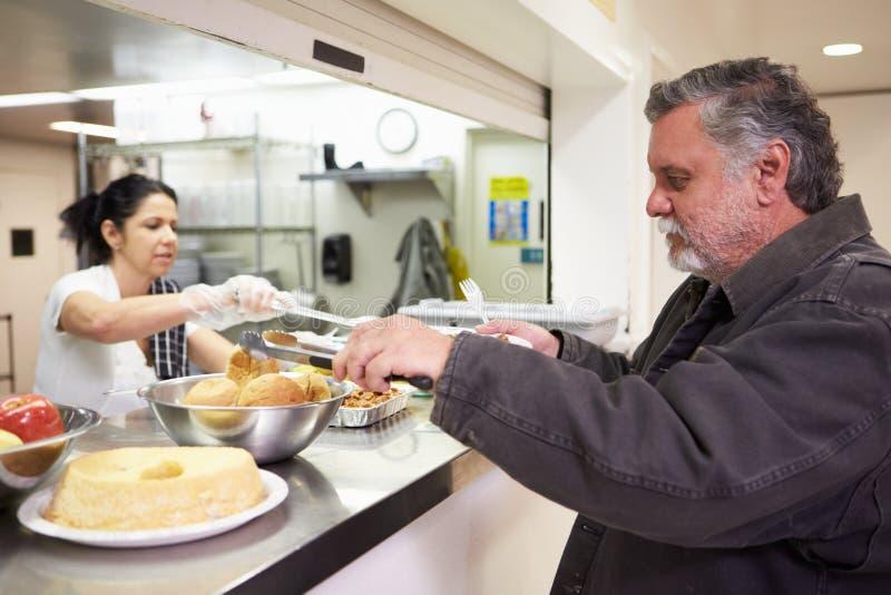 Comida de la porción de la cocina en refugio para personas sin techo foto de archivo