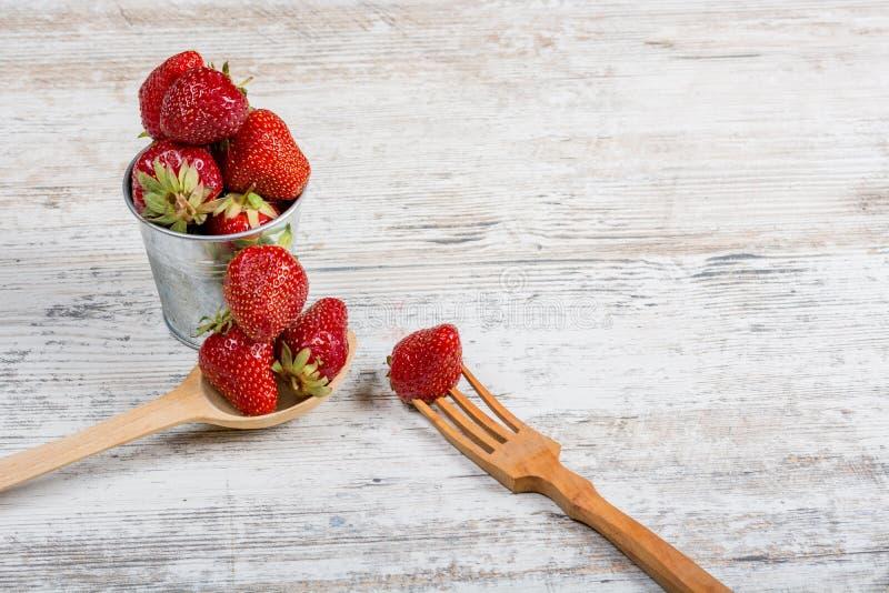 Comida de la vitamina del verano Un cubo de fresas fragantes maduras frescas y una cuchara y una bifurcación de madera foto de archivo