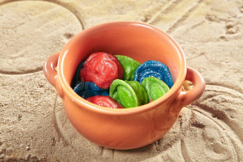 Comida de los niños con las bolas de masa hervida, los raviolis o Pelmeni coloreados en pote de cerámica natural imagen de archivo