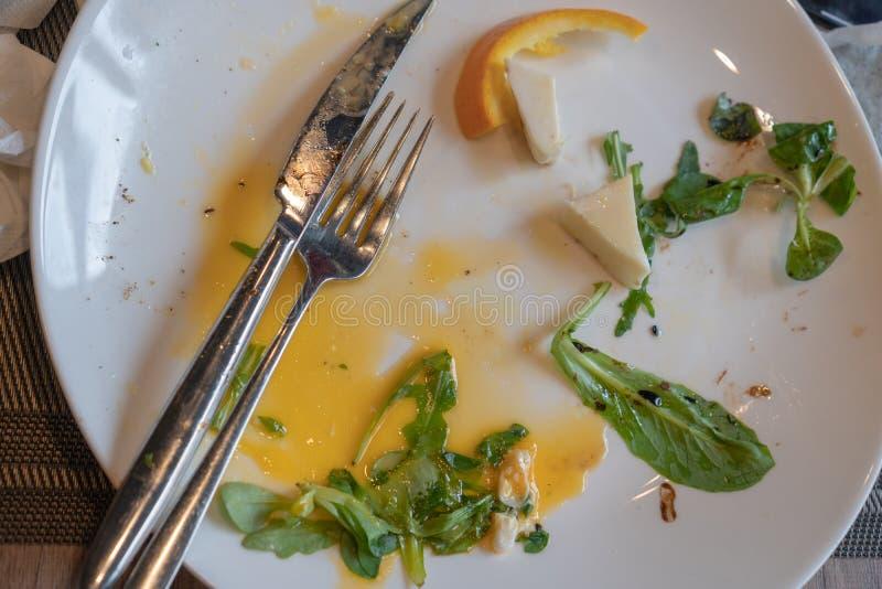 Comida de sobra en una placa sucia La cena ha terminado imagen de archivo