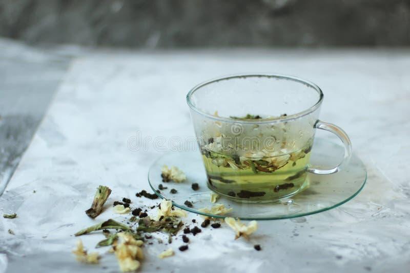 Comida del Detox y beber concepto healfhy de la forma de vida Taza de cristal de té verde con el jazmín en un fondo gris cierre imagen de archivo