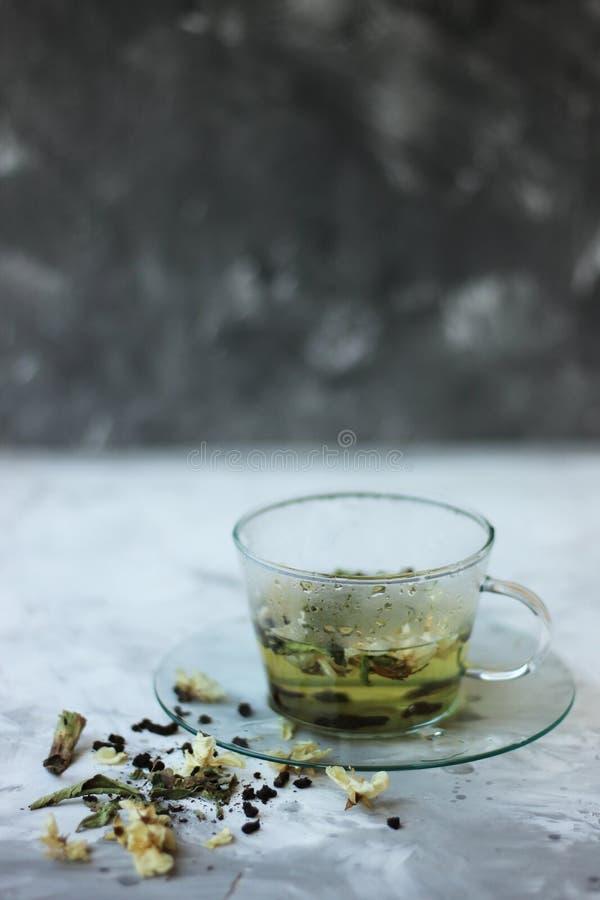 Comida del Detox y beber concepto healfhy de la forma de vida Taza de cristal de té verde con el jazmín en un fondo gris cierre imagen de archivo libre de regalías