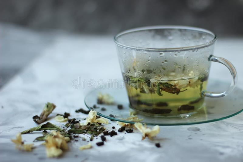 Comida del Detox y beber concepto healfhy de la forma de vida Taza de cristal de té verde con el jazmín en un fondo gris cierre imagenes de archivo