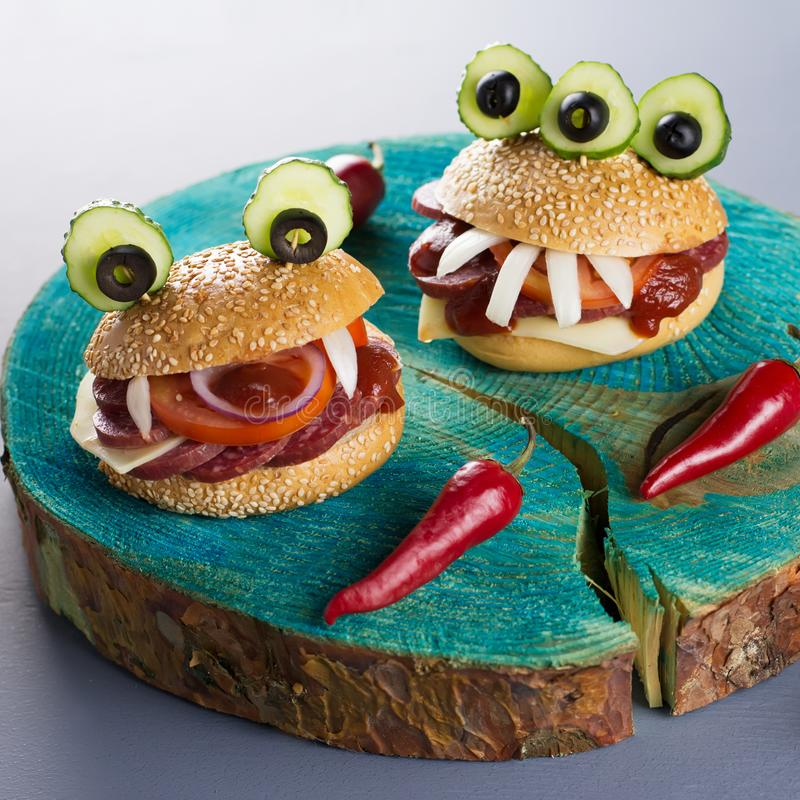 Comida del partido de Halloween Las hamburguesas del monstruo se cierran para arriba con pimientas de chile rojo fotografía de archivo
