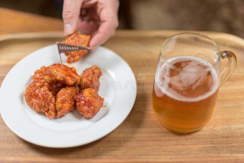 Comida del partido del fútbol - alas y cerveza calientes imagenes de archivo
