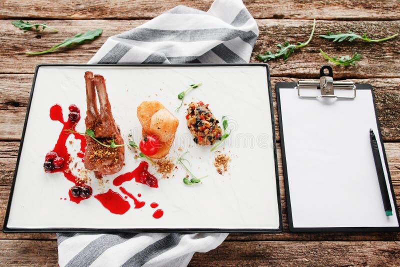 Comida del restaurante costoso con la libreta en blanco imagenes de archivo