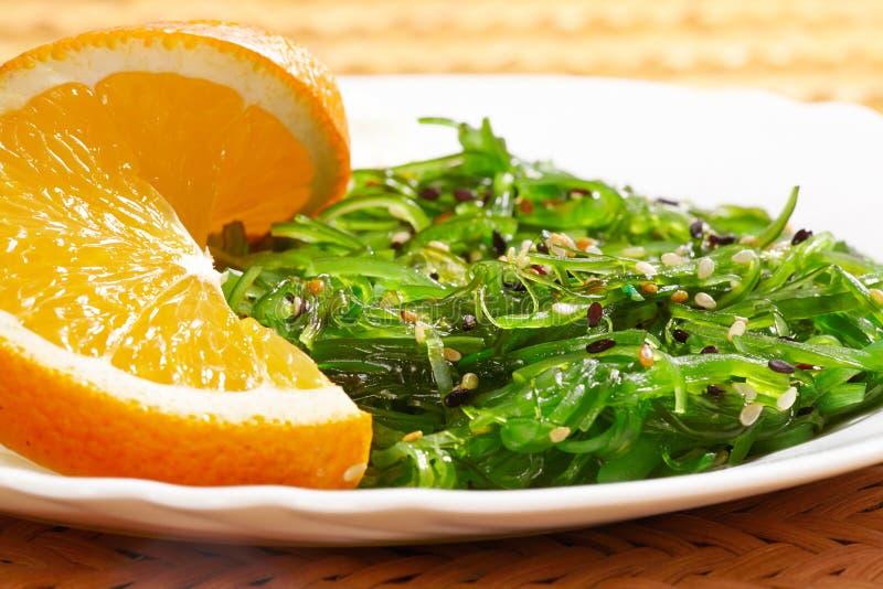 Comida del vegano Cocina japonesa Ensalada de la alga marina con la naranja en la placa blanca fotografía de archivo libre de regalías