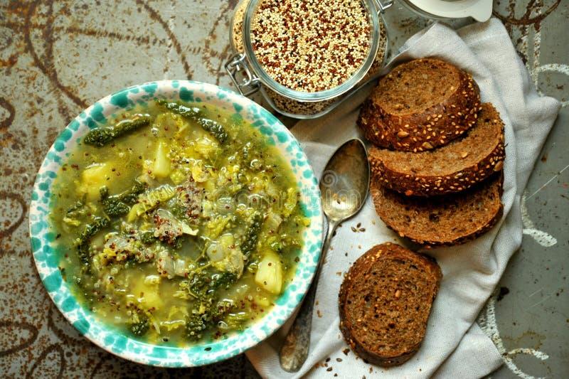 Comida del vegano: sopa de la quinoa con la col y las patatas orgánicas imagenes de archivo