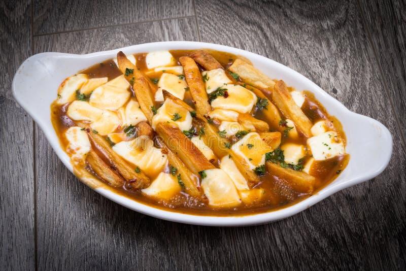 Comida deliciosa del poutine del restaurante en la tabla fotos de archivo