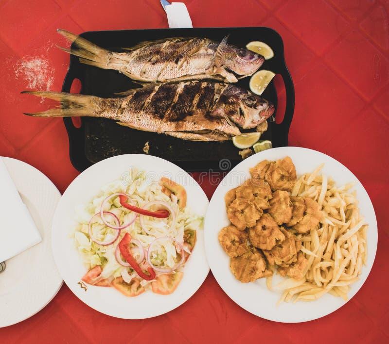 Comida dominicana t?pica durante almuerzo en la playa: los pescados asados a la parrilla con la ensalada, las fritadas y los tost imagen de archivo