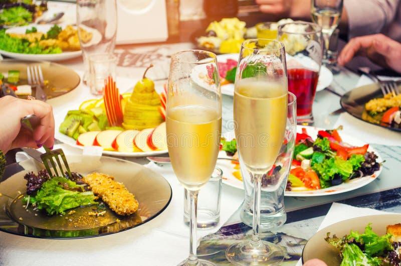 Comida en la tabla, visión muy sabrosa y apetitosa, superior, vidrios de champán imagen de archivo