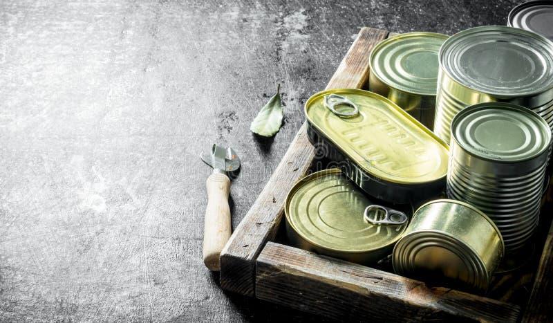 Comida enlatada en latas en una bandeja de madera foto de archivo libre de regalías