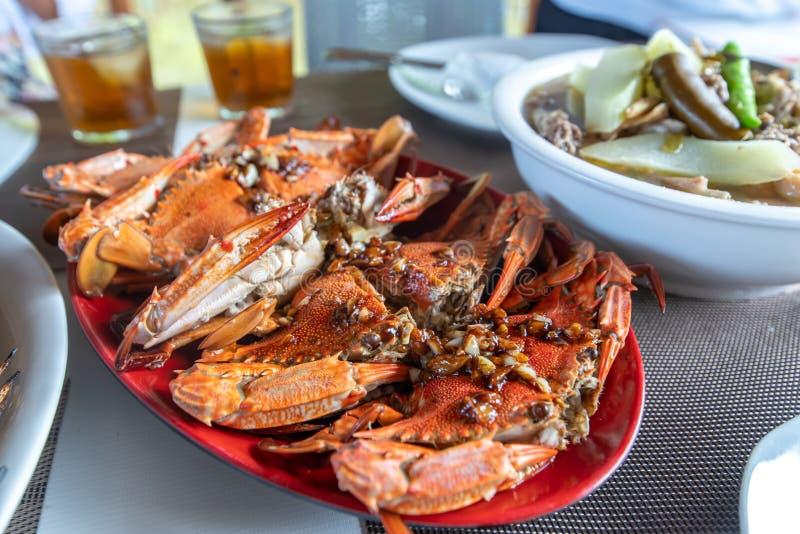 Comida filipina tradicional - cangrejo cocido al vapor del mar con fuente del ajo fotografía de archivo