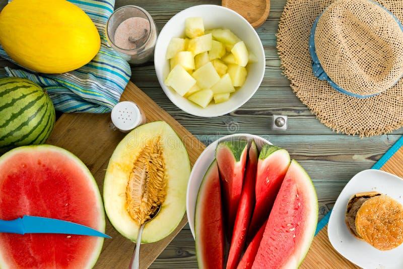 Comida fría del melón en una mesa de picnic de madera imagen de archivo