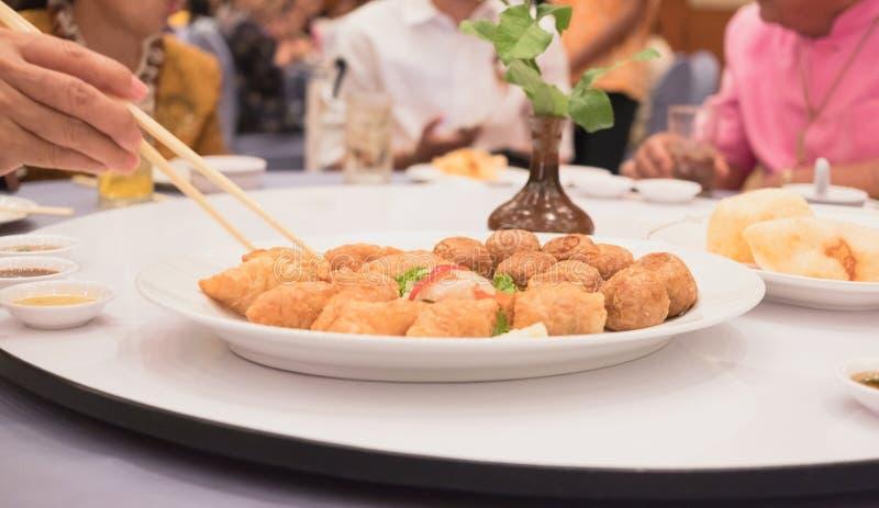 Comida frita en la mesa de comedor con la mano que sostiene los palillos para coger la albóndiga dentro del fondo del restaurante fotografía de archivo