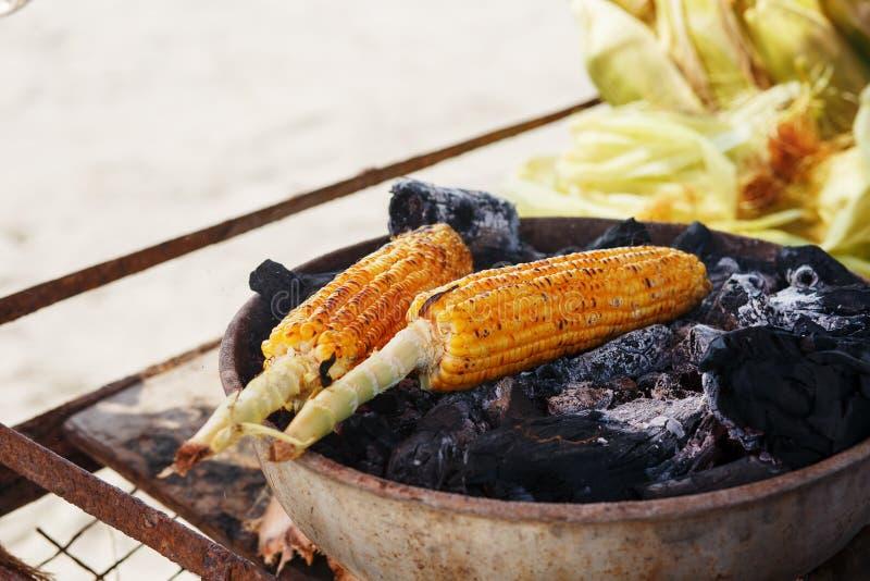 Comida india en la playa - las mazorcas de maíz frescas se asan en los carbones Playa en la puesta del sol de GOA fotos de archivo