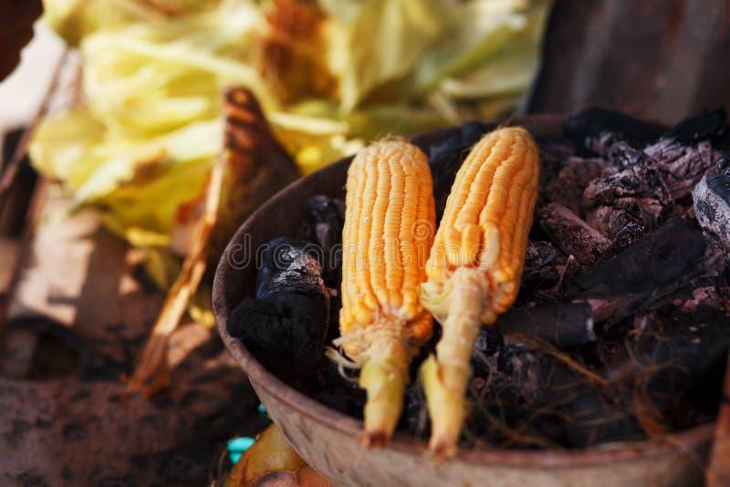 Comida india en la playa - las mazorcas de ma?z frescas se asan en los carbones imagen de archivo