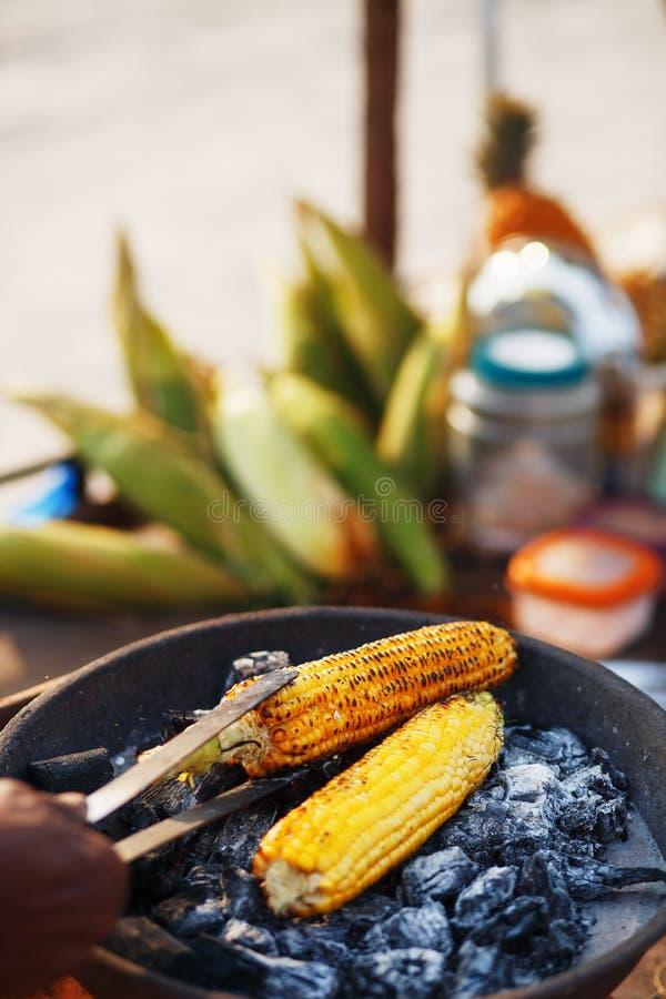 Comida india en la playa - las mazorcas de ma?z frescas se asan en los carbones fotos de archivo libres de regalías