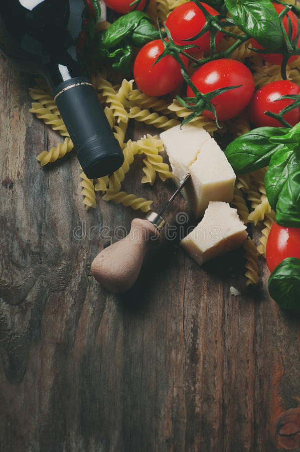 Comida italiana con el fusilli crudo, tomate, albahaca, queso fotografía de archivo libre de regalías
