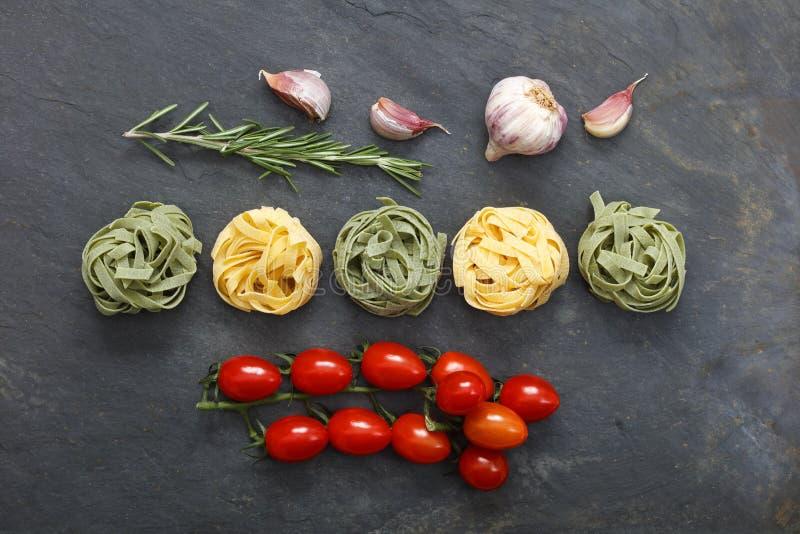 Comida italiana de las pastas con tallarines con los mini tomates y ajo de ciruelo imagenes de archivo