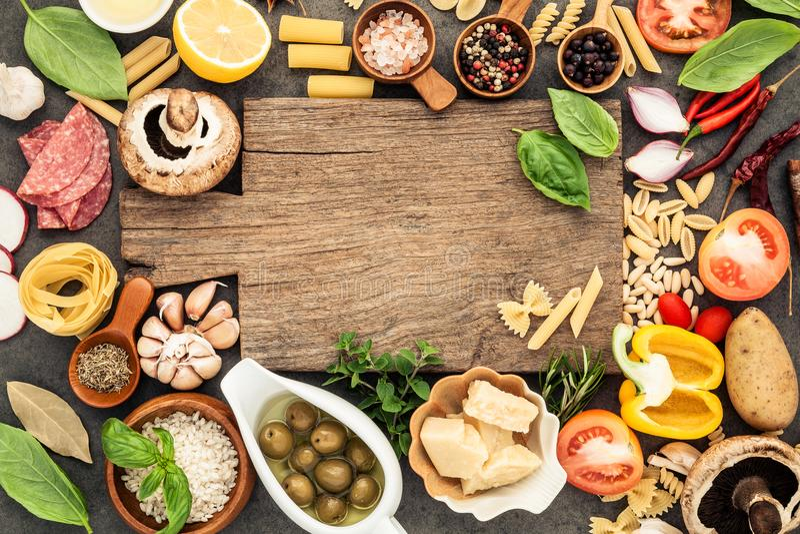Comida italiana que cocina los ingredientes en fondo de piedra oscuro con c fotografía de archivo libre de regalías