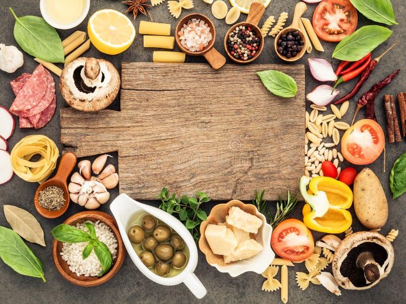 Comida italiana que cocina los ingredientes en fondo de piedra oscuro con c imágenes de archivo libres de regalías