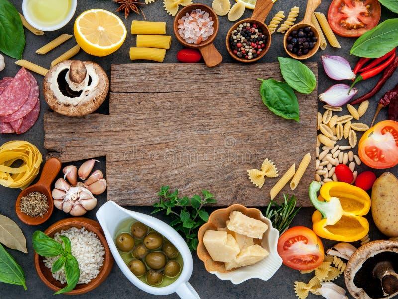 Comida italiana que cocina los ingredientes en fondo de piedra oscuro con c foto de archivo libre de regalías