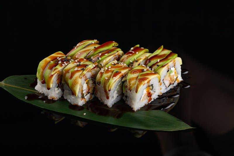 Comida japonesa de los rollos de sushi sobre fondo negro Rollo de sushi con los salmones, el queso de soja, las verduras y el pri foto de archivo