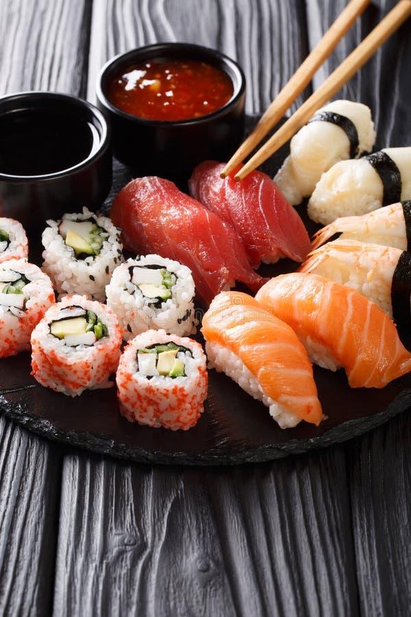Comida japonesa del sushi servida en la placa de la pizarra Rollo de sushi con la gamba, aguacate, salmón, atún, primer del sésam imagen de archivo libre de regalías