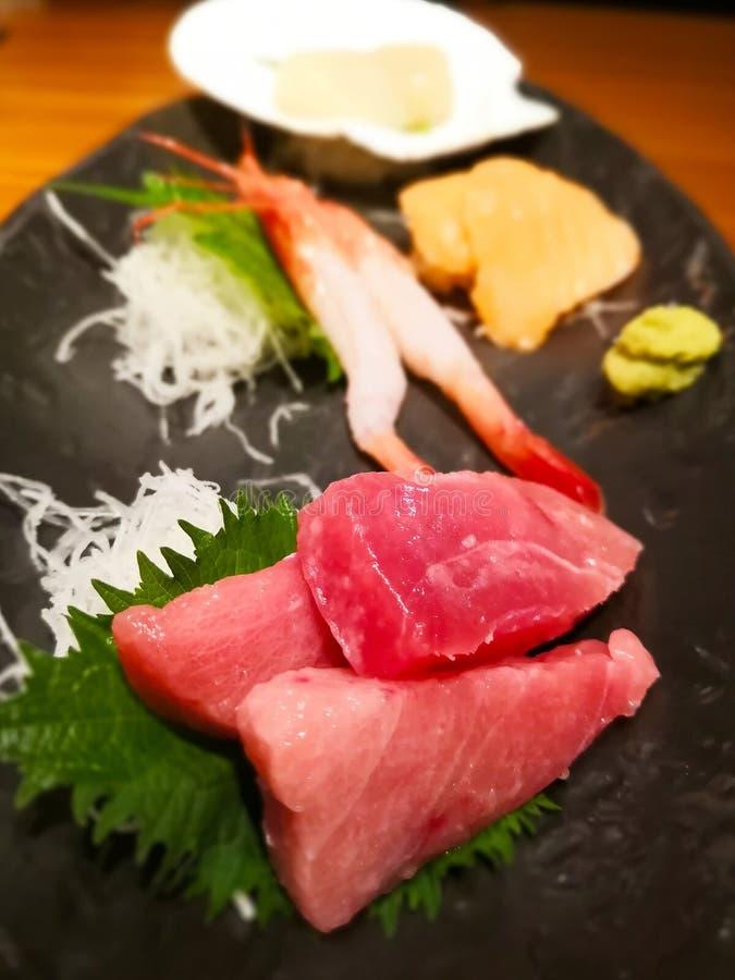 Comida japonesa nacional: placa negra, en ella sashimi del atún crudo, camarones, conchas de peregrino con el daikon cortado en t imagen de archivo