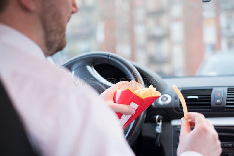 Comida lixo antropófaga e condução assentadas no carro imagens de stock royalty free