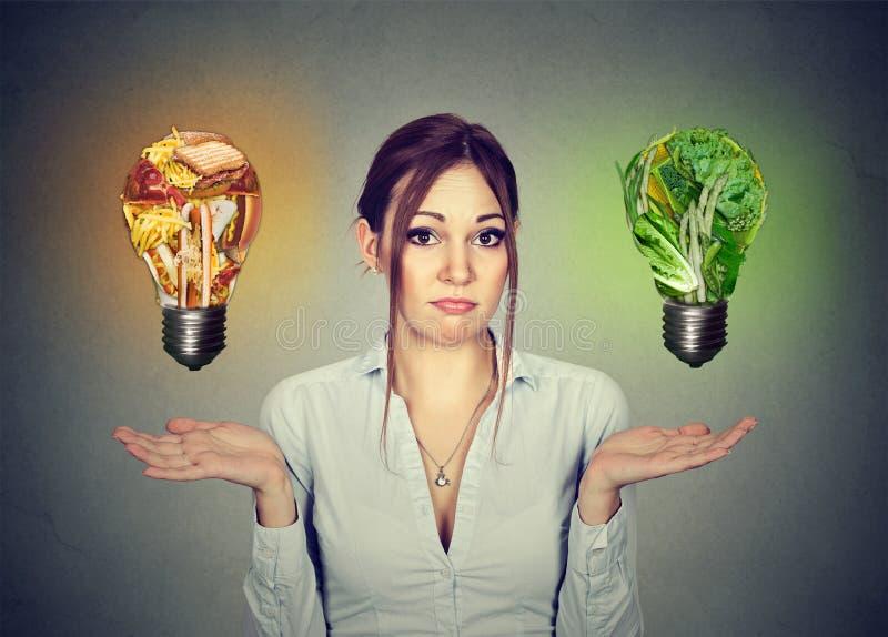 Comida lixo bem escolhida da dieta incerta da mulher ou ampola dos vegetais imagens de stock