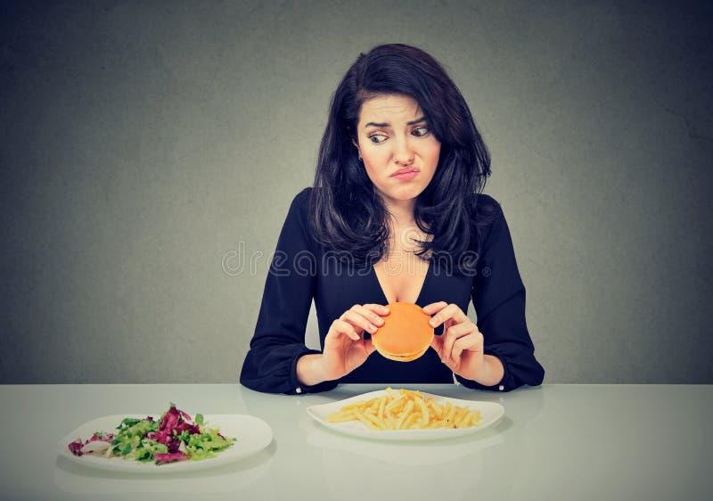 Comida lixo CONTRA o alimento saudável Mulher hesitante com o cheeseburger que olha a salada dos vegetais imagem de stock