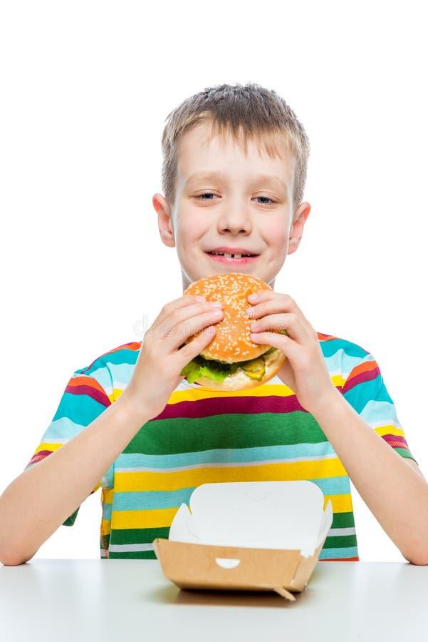 comida lixo da foto do conceito - um menino com um Hamburger em um branco fotos de stock royalty free