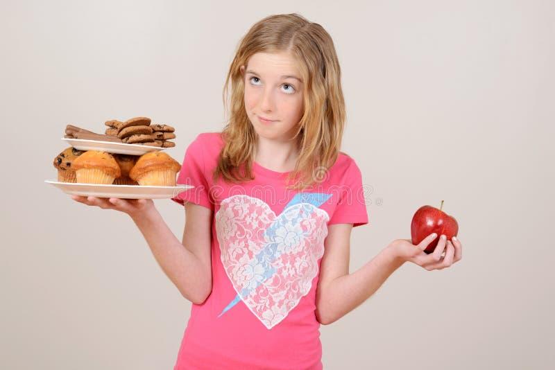 Comida lixo ou maçã de decisão da rapariga fotografia de stock royalty free