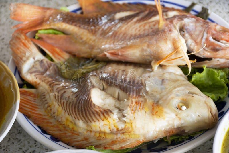 comida local tailandesa estilo sureño Tilapia rojo al vapor Pescado con hierba de verduras en plato y salsa agria picante para el foto de archivo