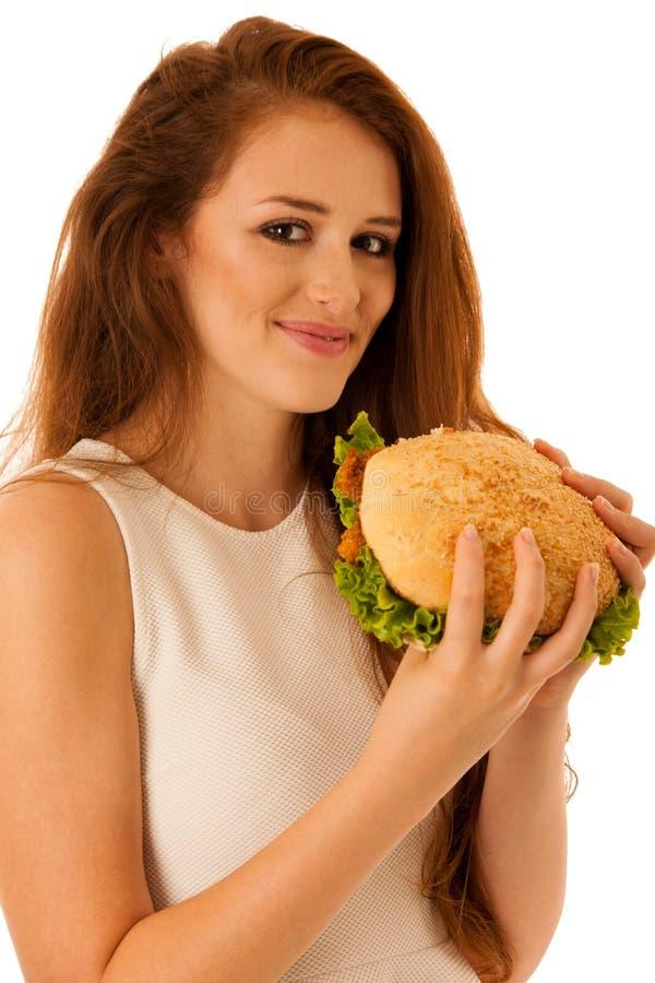 Comida malsana - la mujer joven feliz come la hamburguesa aislada encima imagen de archivo