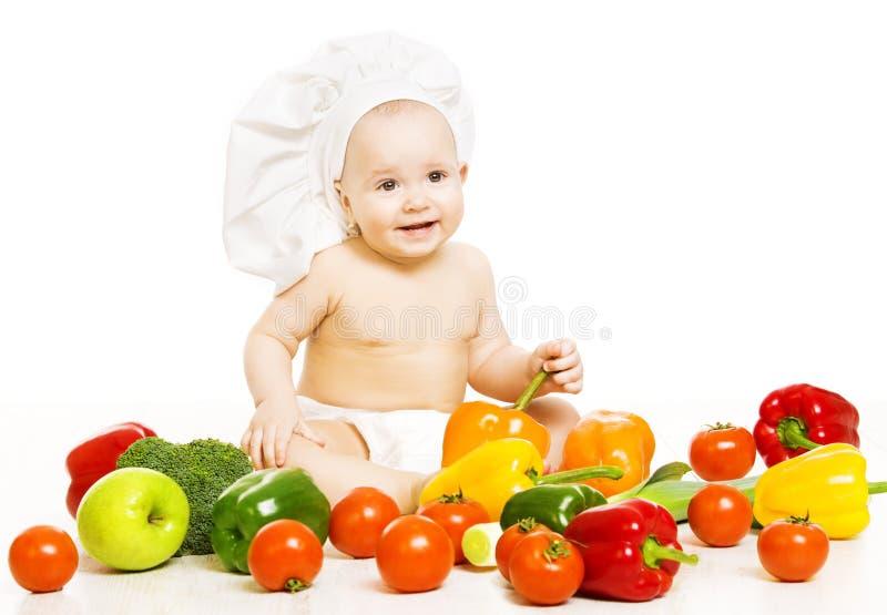 Comida para bebé Criança no chapéu do cozinheiro que senta-se dentro do vegetal sobre o branco imagem de stock royalty free