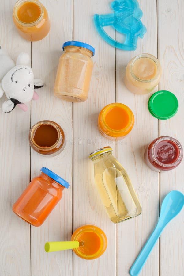 Comida para bebê, colher e brinquedos imagens de stock