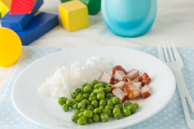 Comida para bebê: costoleta e ervilhas verdes desbastadas imagens de stock royalty free