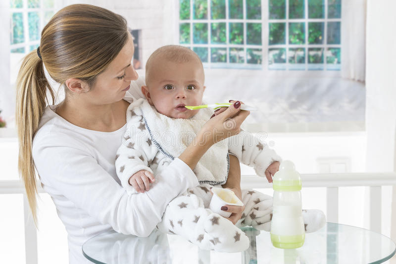 Comida para bebê de alimentação da mãe fotografia de stock royalty free