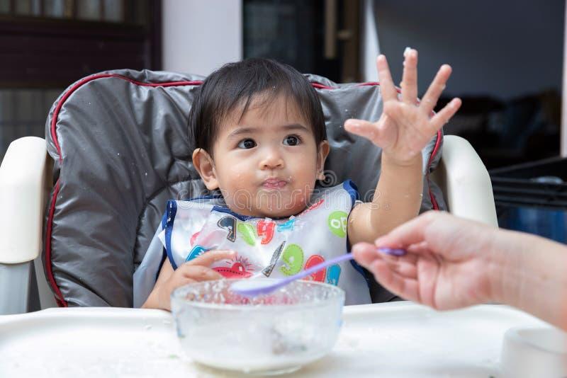 Comida para bebê de alimentação da mãe a sua criança foto de stock