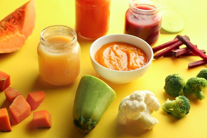 Comida para bebê e ingredientes saudáveis na tabela de cor fotografia de stock royalty free