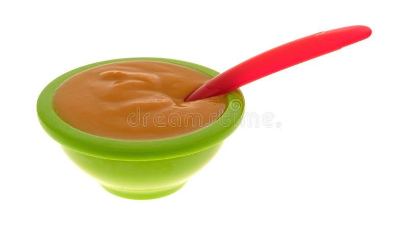 Comida para bebê em uma bacia verde com uma colher fotos de stock