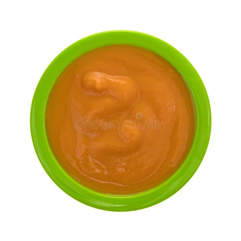 Comida para bebê em uma bacia verde em um fundo branco imagem de stock