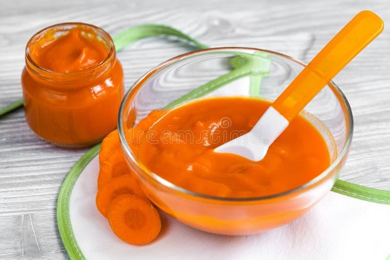 Comida para bebê - puré da cenoura no fundo de madeira fotos de stock royalty free