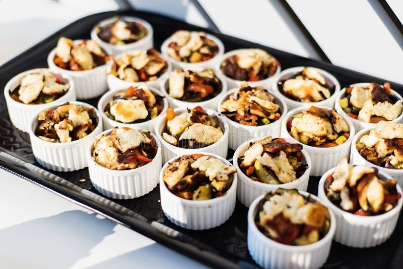 Comida para comer con los dedos (aperitivos) - pequeños ramekins con la ensalada del queso fotografía de archivo libre de regalías