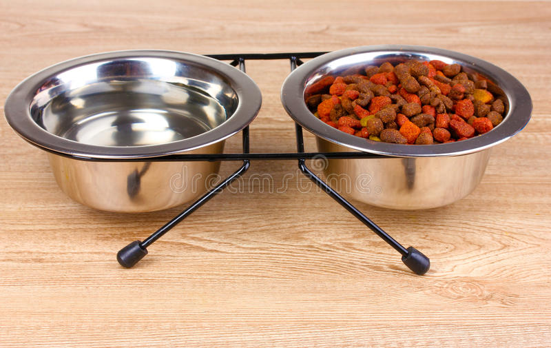 Comida para gatos y agua secas en tazones de fuente en de madera fotos de archivo