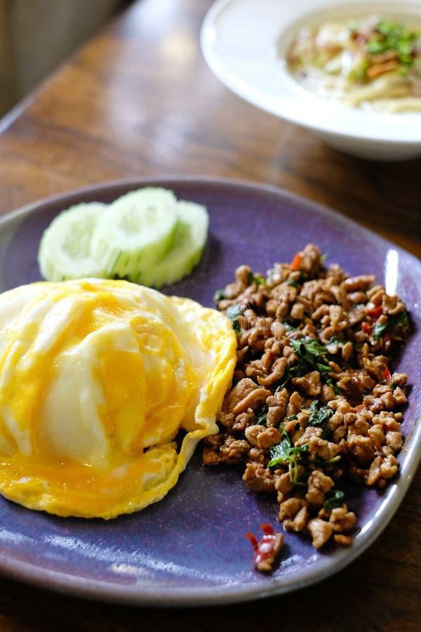 Comida picante, arroz sofrito, cerdo picadito y albahaca rematados con el huevo frito imagenes de archivo