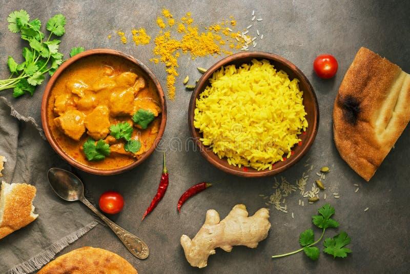 Comida picante de la carne del curry del masala del tikka del pollo, arroz y pan naan en un fondo r?stico marr?n Plato indio y BR fotografía de archivo